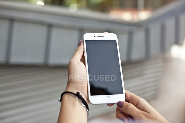 Female hands holding smartphone — Stock Photo