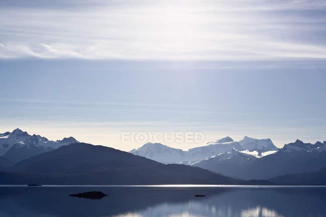 Paisaje con picos de montañas y lago - foto de stock