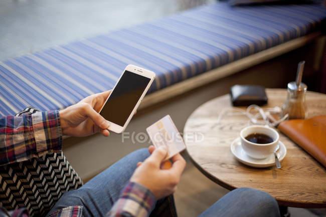 Uomo in possesso di smartphone e biglietto da visita — Foto stock