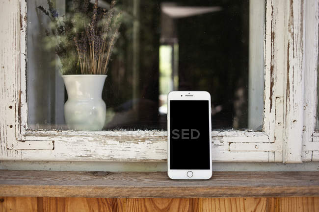 Smartphone on window sill — Stock Photo