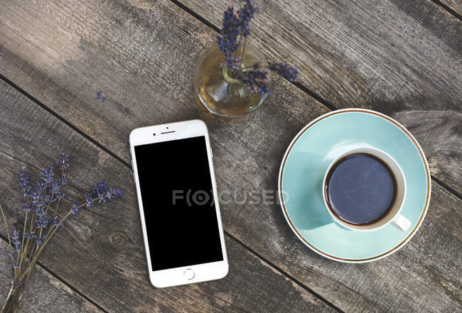 Smartphone and coffee cup — Stock Photo