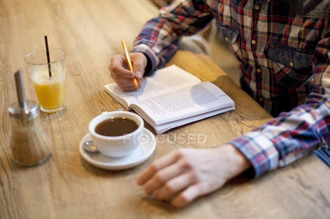 Man making notes in book — Stock Photo