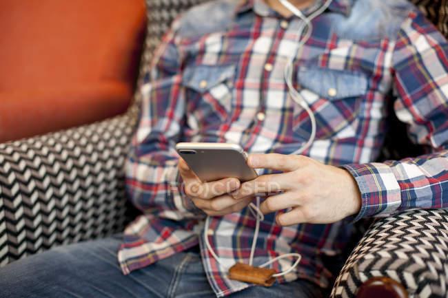 Человек в наушниках и со смартфоном в руках — стоковое фото