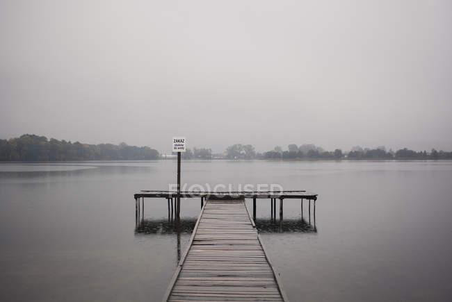 Деревянный пирс и озеро при туманном дневном свете — стоковое фото