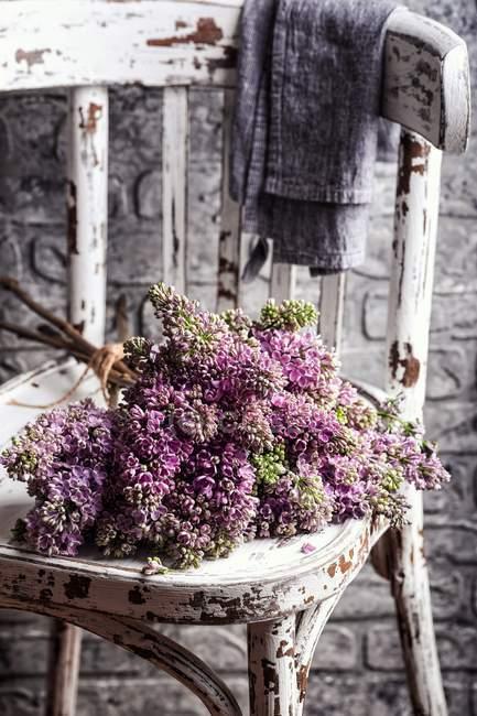 Lilas frais sur une chaise — Photo de stock