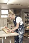 Female designer working with brush — Stock Photo