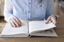 Vista recortada de la mujer sentada en el escritorio con el libro abierto - foto de stock