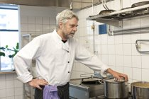 Male chef cooking in restaurant kitchen interior — Stock Photo