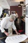 Male chef preparing opening hours banner in restaurant interior — Stock Photo