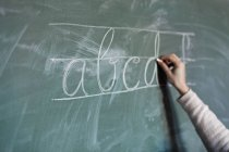 Hand writing letters on chalkboard — Stock Photo