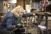 View of female glassblower at work in workshop — Stock Photo