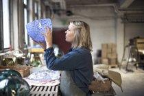 Vue de côté de femme regardant produit verrier dans l'atelier de souffleur de verre — Photo de stock