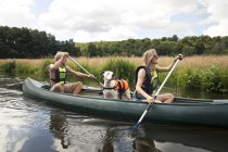 Man and woman canoeing with amstaff dog in life vest — Stock Photo