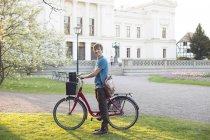Male student standing in university campus yard with bike and leather suitcase — Stock Photo
