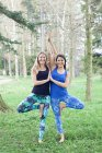 Zwei Frauen im Yoga-Baum posieren zusammen mit pressenden Handflächen — Stockfoto
