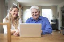 Woman teaching grandfather using laptop — Stock Photo