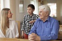 Дідусь, сидячи в домашній інтер'єр з онуками — стокове фото