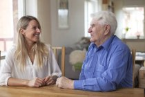 Senior man speaking with smiling granddaughter in home interior — Stock Photo