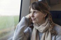 Женщина с косичками, выглядывающая из окна поезда — стоковое фото