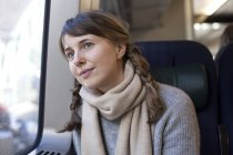 Woman with braid pigtails looking out of train window — Stock Photo