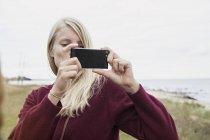 Femme blonde au bord de mer prendre photo avec smartphone — Photo de stock