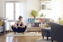 Donna che guarda il gatto durante lo yoga — Foto stock