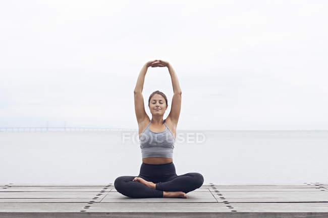 Женщина в позы йоги по морю — стоковое фото