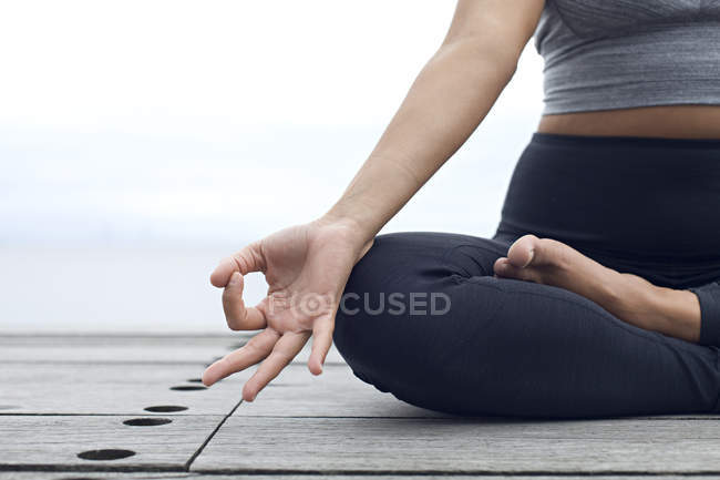 Woman in yoga posture by sea — Stock Photo