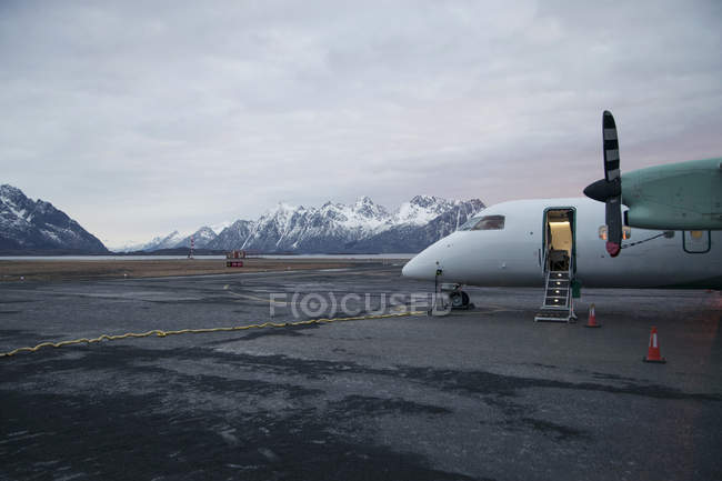 Arplane at airport in mountains landscape — Stock Photo
