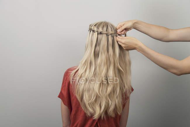 Плетение волос блондинки руки — стоковое фото