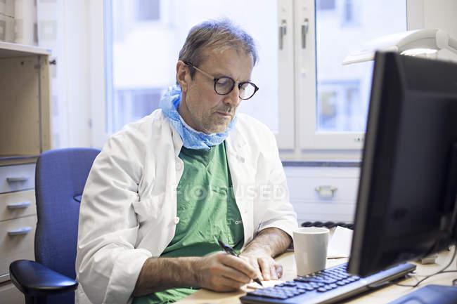 Surgeon writing on desk — Stock Photo