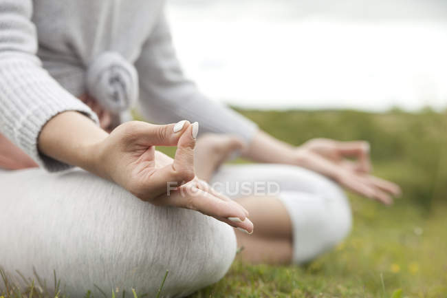 Woman meditating on meadow — Stock Photo