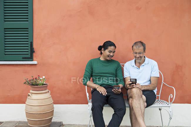 Uomini che esaminano i telefoni — Foto stock