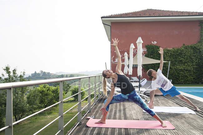 Gente che fa yoga vicino alla piscina — Foto stock