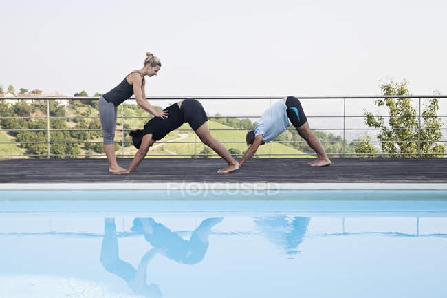 Studenti correggente di insegnante di yoga — Foto stock