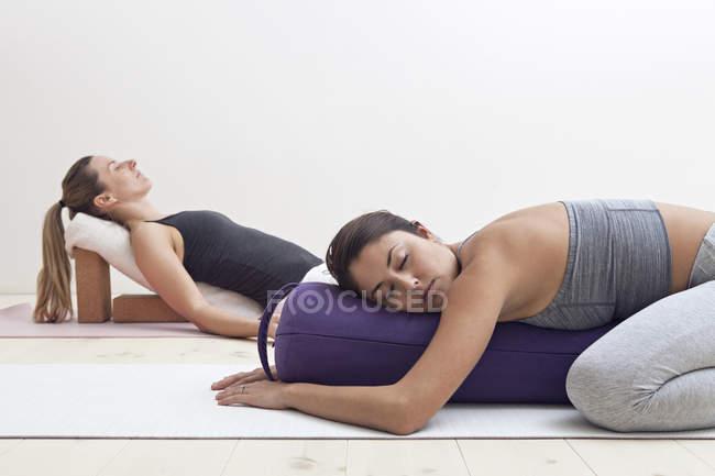 Женщины в позах восстановительной йоги — стоковое фото