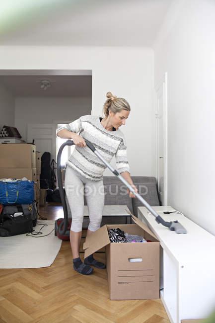 Estante con la aspiradora mujer durante traslado - foto de stock