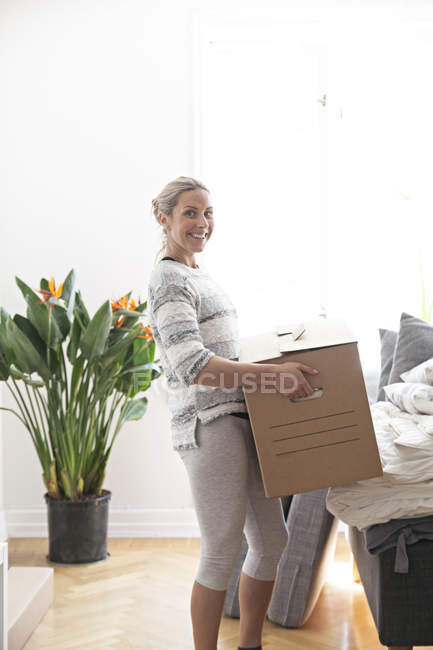 Woman carrying cardboard box — Stock Photo