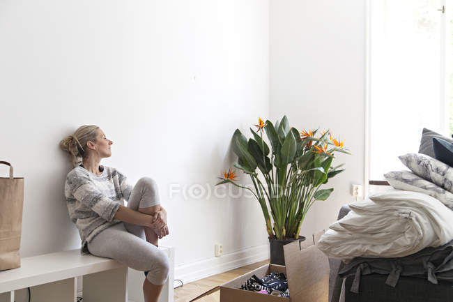 Woman sitting by open box during relocation — Stock Photo
