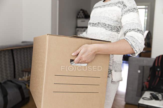 Mujer sosteniendo la caja de cartón - foto de stock