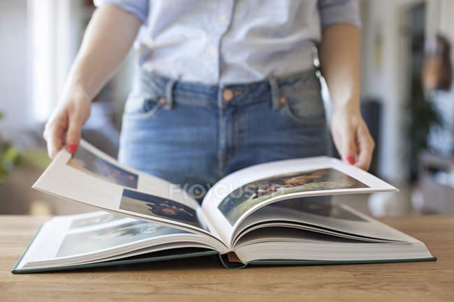 Обрезанный вид женщины, стоя на стол с открытой книгой — стоковое фото