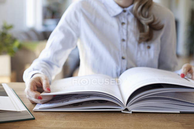 Cropped view of woman sitting at desk with open book — Stock Photo