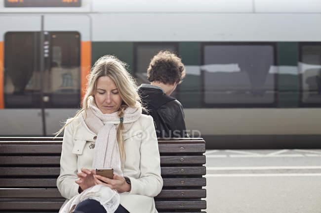 Blonde Frau auf dem Zug Bahnhof Bank sitzen und mit smartphone — Stockfoto