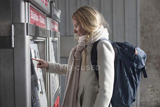 Vista laterale del turista femminile acquisto biglietto del treno — Foto stock