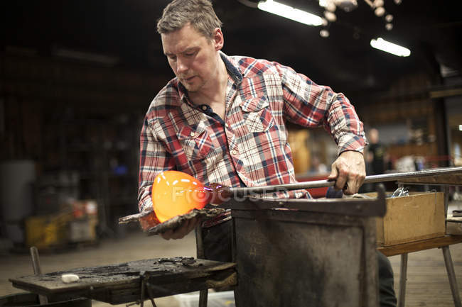 Glassblower working with molten glass — Stock Photo