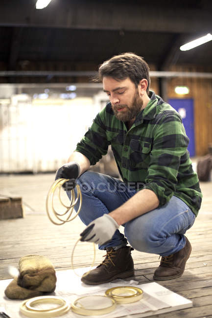 Man arranging crafting parts in workshop — Stock Photo