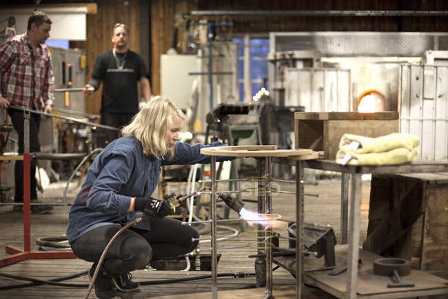 View of female glassblower at work with colleagues — Stock Photo