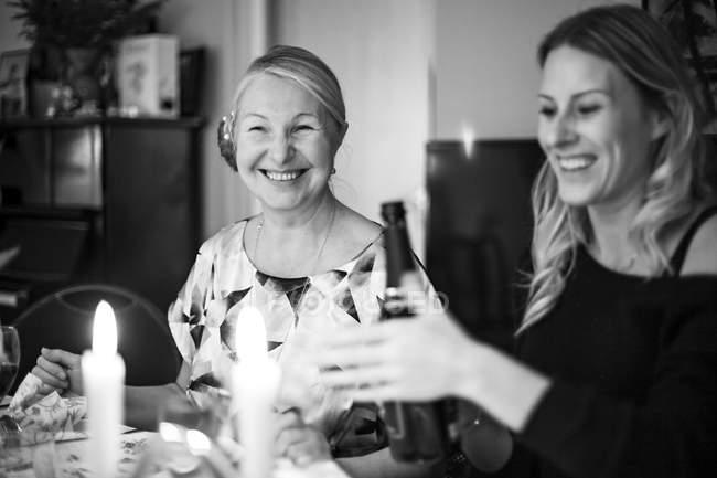 Женщина, открывающая бутылку вина за столом со зрелой матерью — стоковое фото