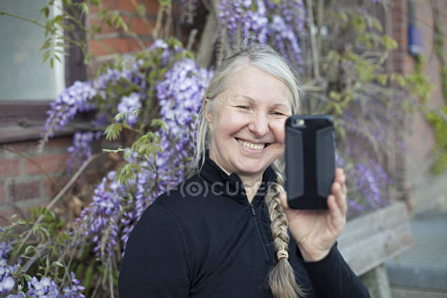 Senior woman filming with smartphone on street — Stock Photo