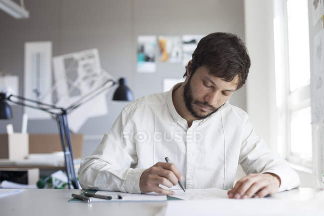 Male architect sketching at workplace — Stock Photo